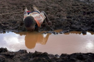 June 12, 2009: A boy drinks water from a pond in Bule Duba village, near the edge of Oroma and Somali regions of Ethiopia(Irada Humbatova/Reuters)